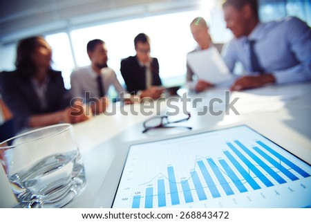 Paper with charts and glass of water on background of working colleagues - stock photo