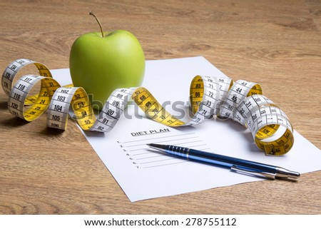 paper with diet plan, apple and measure tape on wooden table - stock photo