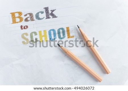 Paper with inscription word BACK TO SCHOOL near wooden pencil with copy space, idea concept, education concept