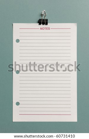Paper with lines hanging from a clip isolated on a green background - stock photo