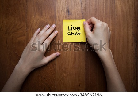 paper with live chat. female hands holding paper note with live chat on wooden background - stock photo