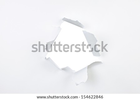 Paper with ripped hole and torn edges over white - stock photo