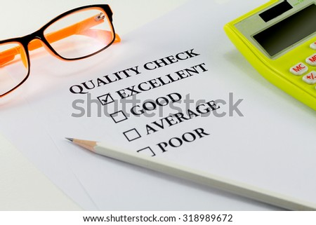 paper with word quality check and white pencil eyeglasses calculator with mark on excellent