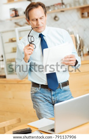 Paper work. Bespectacled occupied busy man standing in the room near the table biting the glasses and reading documents.