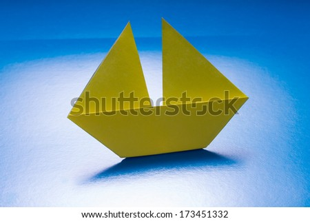 Paper Yellow Boat Sailing on Blue paper sea. Origami Ship - stock photo