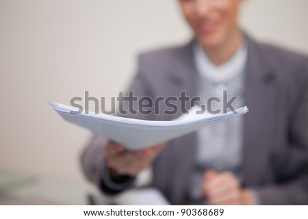 Paperwork being handed over by young businesswoman - stock photo