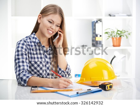 Paperwork in engineer's office. Pretty smiling woman designer drawing sketch of new building sitting at the table with angle, tape and hardhat.  - stock photo