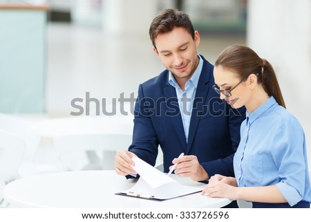 Paperwork routine. Two smiling employees are busy with form-filling maintenance - stock photo