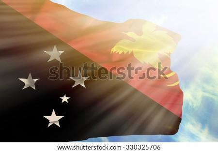 Papua New Guinea waving flag against blue sky with sunrays - stock photo