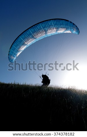 Para glider before the flight, silhouette . Paraglider. Parachuter. Paragliding in mountains. Paragliding sport.Parachute jumper.Parachute. Extreme sports activity - stock photo