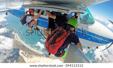 Parachutists hanging off the plane, in a paradise place. - stock photo