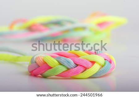 Paracord braided into a decorative knot, in bright neon colors - stock photo