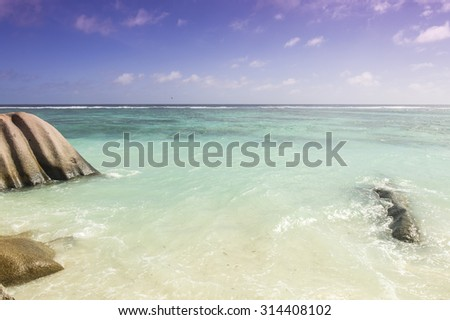 Paradise beach of Seychelles in la Digue island, Anse Source d'Argent. Boulders black granite rocks, turquoise water, white sand and blue sky. - stock photo