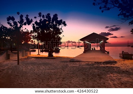 Paradise Maldives beach at pink sunset, glowing light in the restaurant over water, with cople and boats romantic place for honeymoon vacation, summer evening on exotic island, Maldives landscape - stock photo