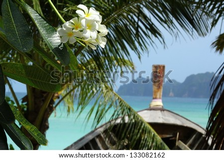 Paradise Thailand / Beautiful Thailand islands shot of the long-tailed boat overlooking the blue ocean, with mono�¯ flowers and palm leafs on the fore-scene
