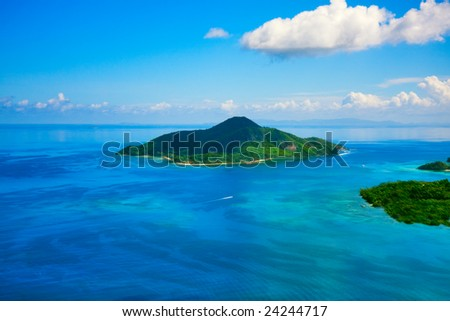 Paradise Tropical Island from above - aerial. Calm exotic beach resort in background - stock photo
