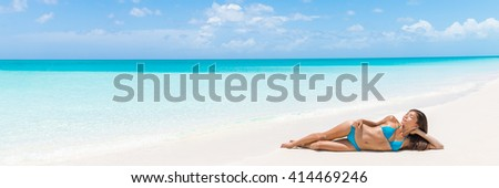 Paradise tropical vacation woman relaxing on perfect white sand beach Caribbean travel destination. Luxury living dreamy getaway Asian skincare model lying down sun tanning in secluded resort. - stock photo