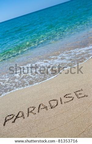 Paradise written on the sand - stock photo