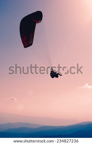 Paraglide silhouette in a sky over Carpathian mountains - stock photo