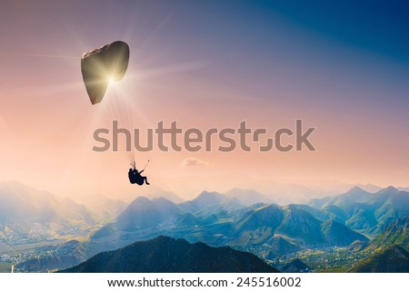 Paraglide silhouette over mountain peaks.  - stock photo