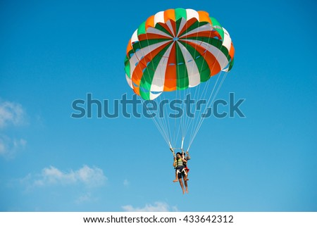 Paraglider flying against the blue sky at sunset time, Blurred background - stock photo