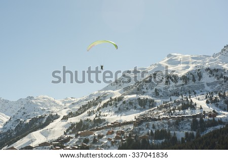 Paraglider flying over a snow covered alpine mountain range looking down valley - stock photo