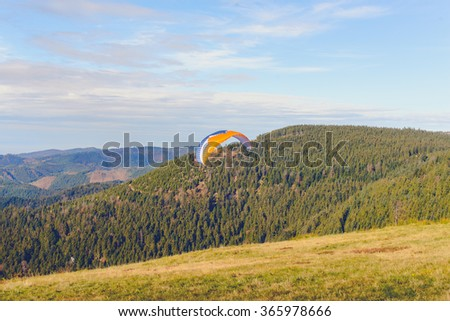 Paraglider flying over mountains in summer day - stock photo
