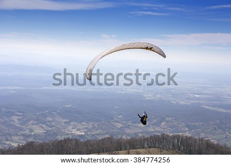 Paraglider flying over mountains to the valley - stock photo