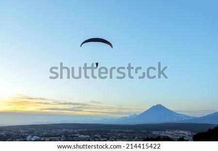 Paraglider flying over vespers Petropavlovsk-Kamch atsky on the background of the volcano Koryaksky at sunset - Kamchatka, Russia - stock photo