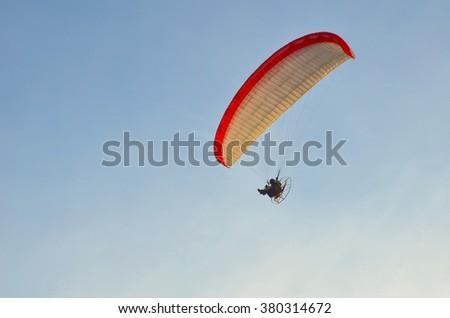 Paraglider in flight in blue sky in summer - stock photo