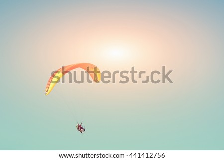 Paraglider in the sunny sky - stock photo