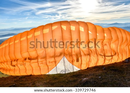 Paraglider is starting. Parachute is filling with air in the mountains alps ona sunny day. - stock photo