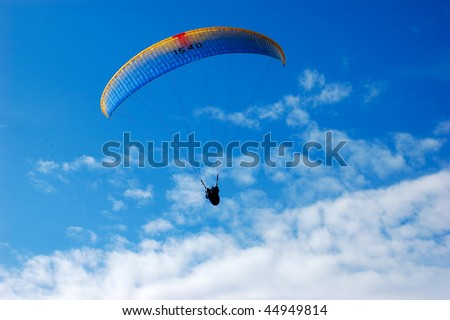 Paraglider on blue sky with feather clouds - stock photo