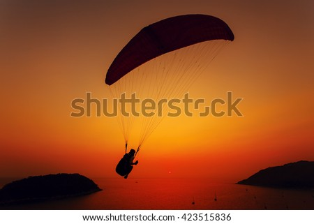 Paraglider silhouette against the background of the sunset sky and sea - stock photo