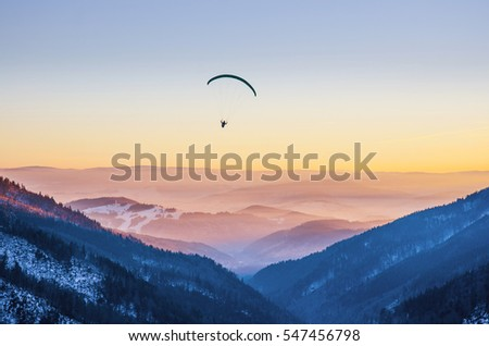 Paraglider Silhouette Flying Over Misty Mountain Valley In Beautiful Warm Sunset Colors