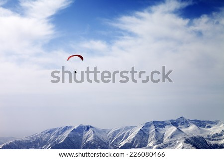 Paraglider silhouette of mountains in windy sky. Caucasus Mountains. Georgia, ski resort Gudauri. - stock photo