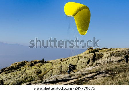 Paraglider tandem prepareing to take off from a mountain - stock photo