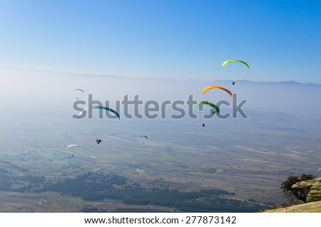 Paragliders at clear blue sky. Paragliding is extreme adrenaline sport. - stock photo