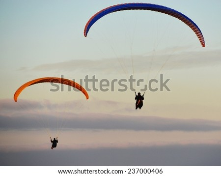 Paragliders Soar through the Warm Evening Sky - stock photo