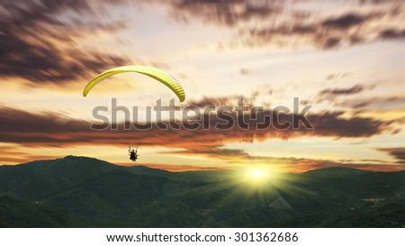 Paragliding at sunset with purple clouds - stock photo