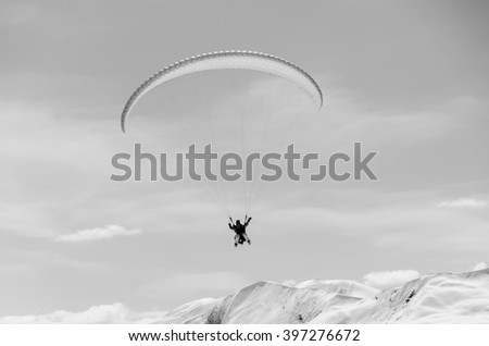 Paragliding in mountains in spring time. Blank space for a text. Black and white picture. Men in the center. Georgia, gudauri