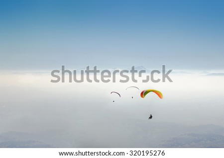 paragliding in nepal with himalaya view and clear blue sky - stock photo