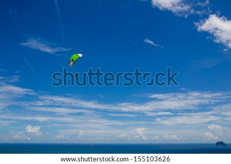 Paragliding in sky over blue sea