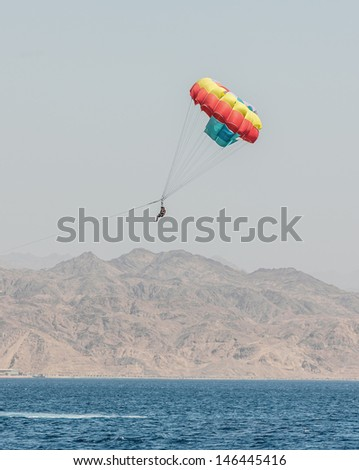 Paragliding in the clear sky above the Red Sea - Eilat, Israel - stock photo