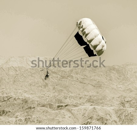 Paragliding in the clear sky above the Red Sea - Eilat, Israel (stelyzed retro) - stock photo