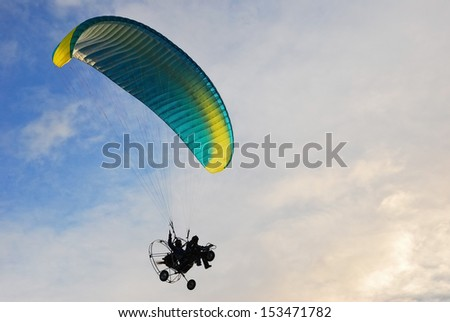Paragliding in the sky and clouds at sunset time - stock photo