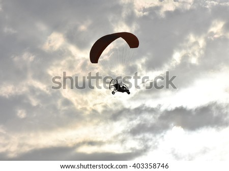 Paragliding on sunset,  silhouette of para-motor glider - stock photo
