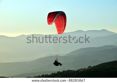 Paragliding pilot with red parachute