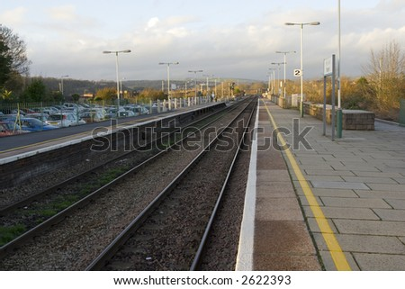Parallel lines and tracks near a British railway station platform - stock photo