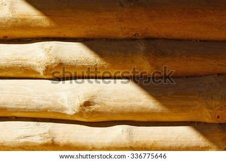 Parallel yellow wooden logs and shadow